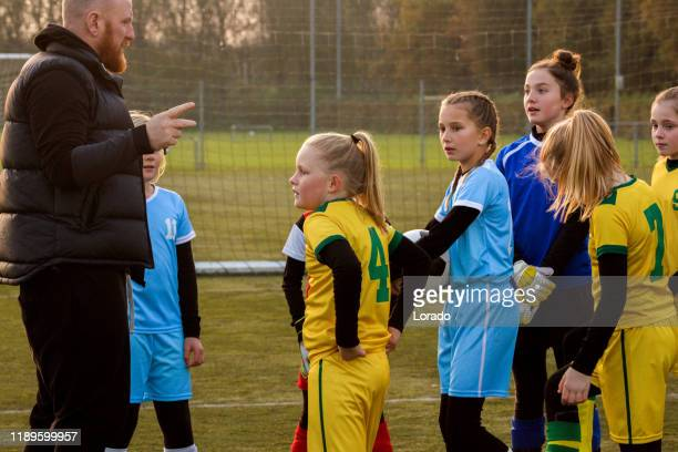 soccer father coaching football daughter's team during a training session - club football stock pictures, royalty-free photos & images