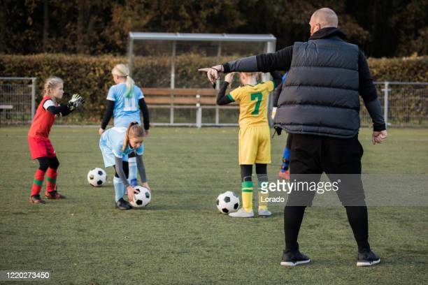 soccer father coaching football daughter's team during a training session - sideline stock pictures, royalty-free photos & images
