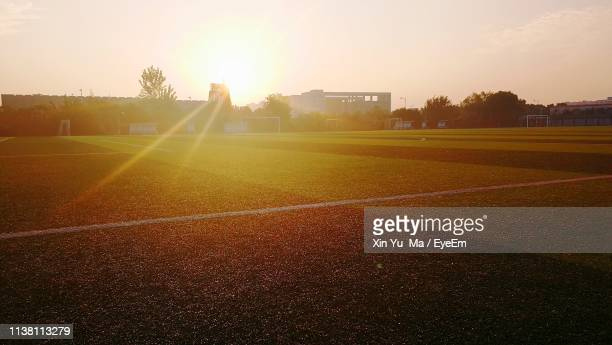 soccer field against sky during sunset - pitch stock pictures, royalty-free photos & images