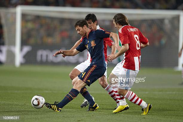 FIFA World Cup Spain Xabi Alonso in action vs Paraguay Edgar Barreto and Victor Caceres during Match 60 Quarterfinals at Ellis Park Stadium...