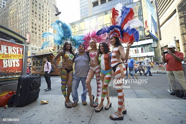 FIFA World Cup View of fan posing for photograph with women wearing national flag body paint in Times Square New York NY CREDIT Kiera Wood