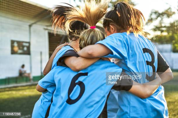 soccer girls huddling after winning match - sports team stock pictures, royalty-free photos & images
