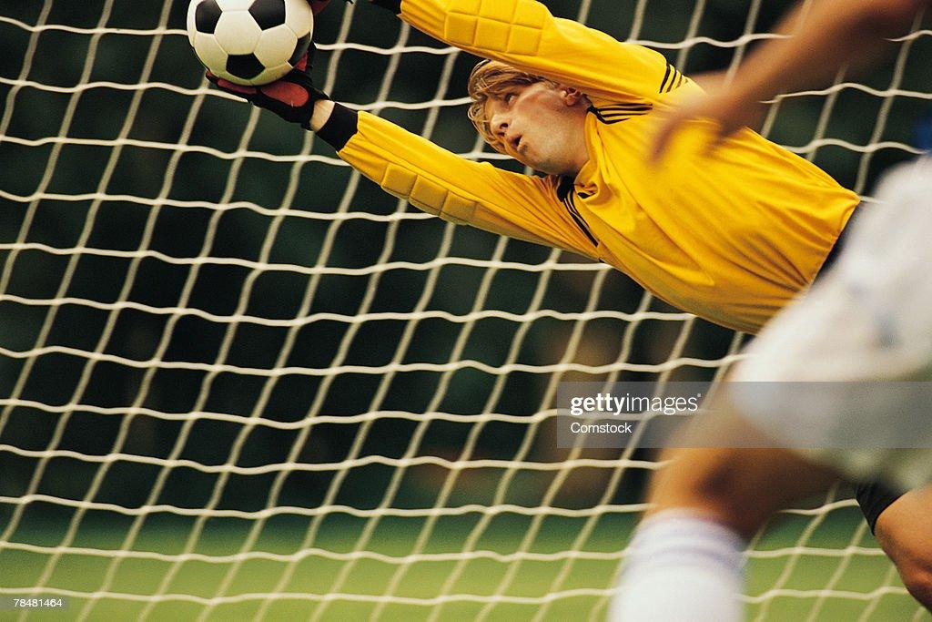 Soccer goalie blocking ball : Stock Photo