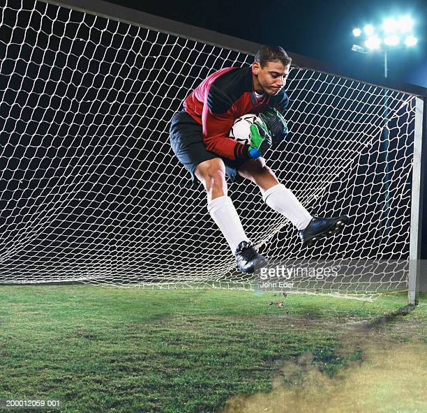 soccer goalie catching ball in mid-air - goalkeeper stock pictures, royalty-free photos & images