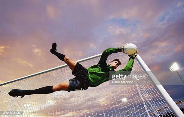 soccer goalie catching ball in mid-air - goalie goalkeeper football soccer keeper stock pictures, royalty-free photos & images