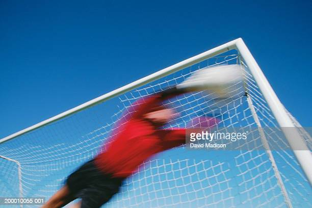 soccer goalie diving for ball, low angle view (blurred motion) - making a save sports stock pictures, royalty-free photos & images