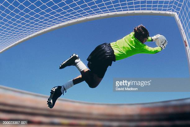 Soccer goalie leaping to catch ball (selective focus)
