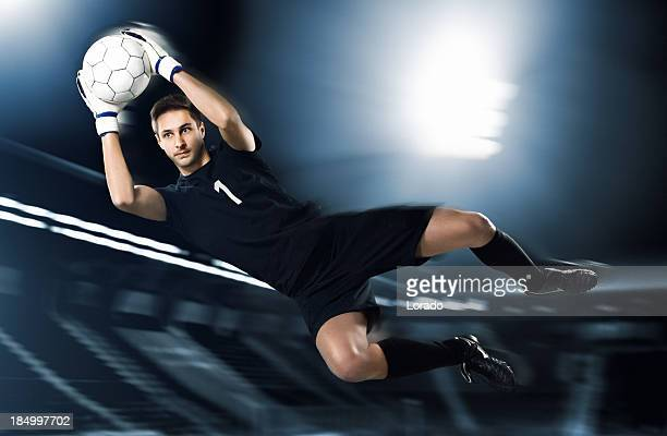 soccer goalkeeper catching ball in mid-air - goalie goalkeeper football soccer keeper stock pictures, royalty-free photos & images