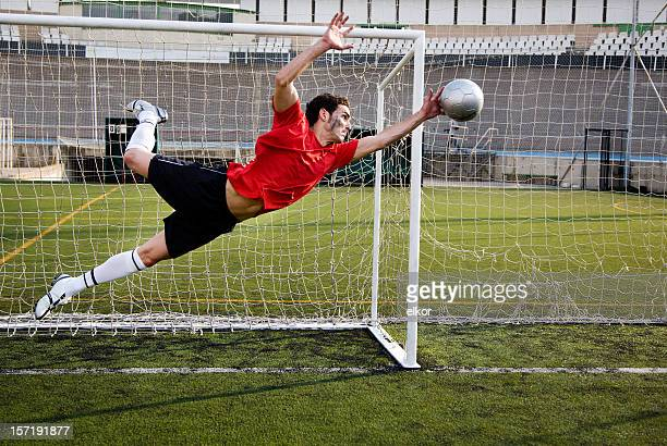 soccer goalkeeper catching the ball. - goalie goalkeeper football soccer keeper stock pictures, royalty-free photos & images