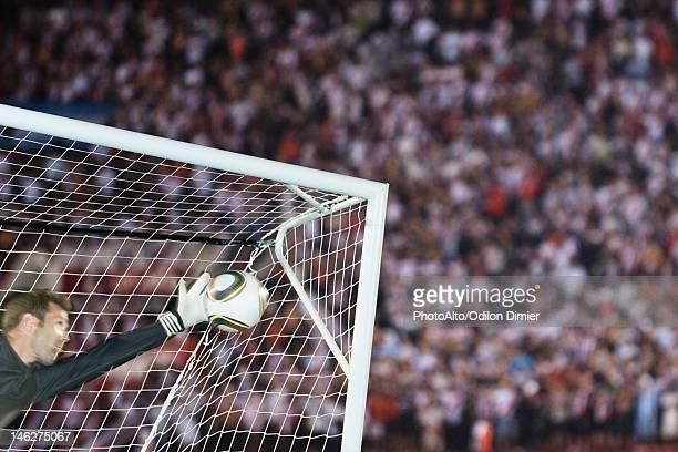 Soccer goalkeeper diving to block ball
