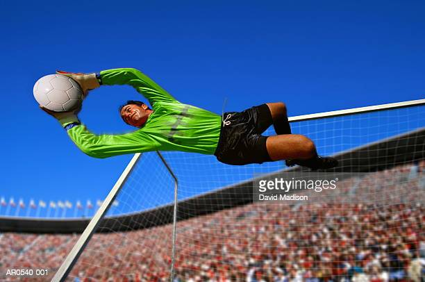 Soccer goalkeeper diving with ball in stadium (Digital Composite)