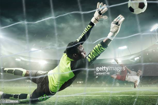 soccer goalkeeper in action at professional stadium. - goalkeeper stock pictures, royalty-free photos & images