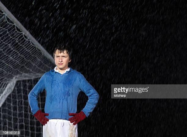 Soccer goalkeeper in rain at night