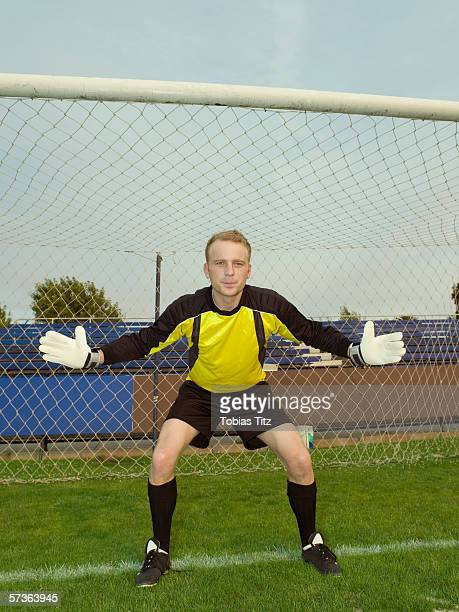 A soccer goalkeeper with his arms out to his sides