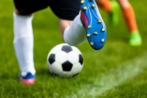 Soccer Kick. Footballer Kicking Ball on Grass Pitch. Football Soccer Player Hits a Ball. Soccer Boots Close Up 956352788