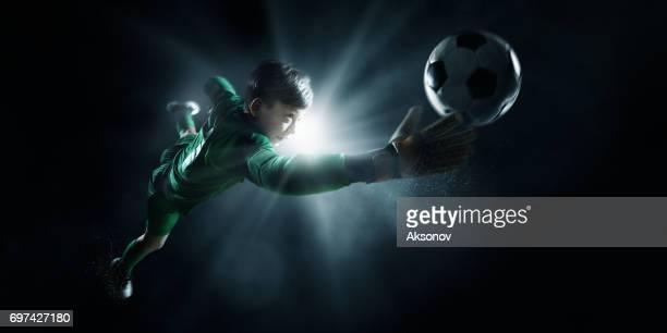 Soccer kids goalkeeper catch the ball in spotlight