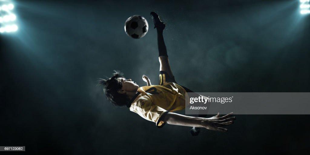 スポット ライトでボールを蹴る子供サッカー : ストックフォト