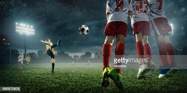 Soccer kids player makes a free kick