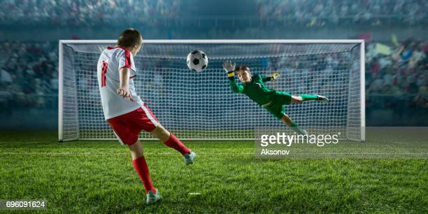 soccer kids player scoring a goal. goalkeeper tries to hit the ball - portiere posizione sportiva foto e immagini stock