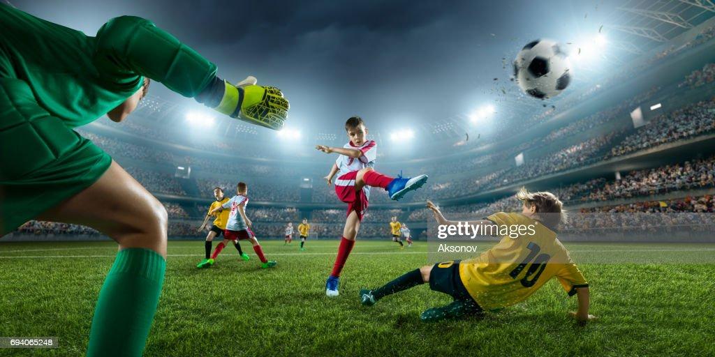 Futebol garotos jogadores marcando um gol. Goleiro tenta acertar a bola : Foto de stock