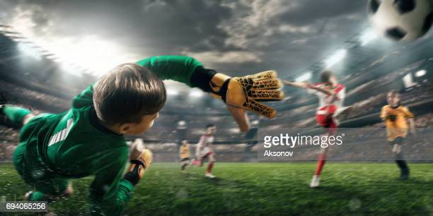 Soccer kids players scoring a goal. Goalkeeper tries to hit the ball