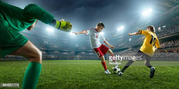 soccer kids players scoring a goal. goalkeeper tries to hit the ball - soccer competition stock pictures, royalty-free photos & images