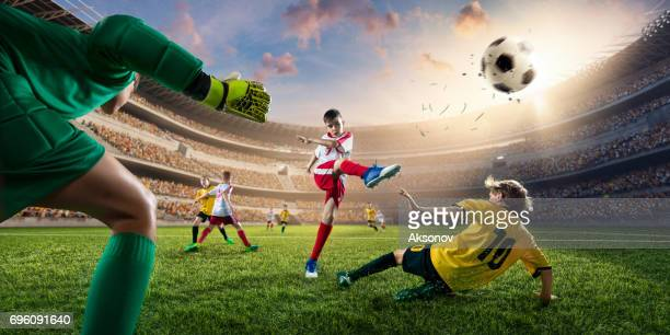 soccer kids players scoring a goal. goalkeeper tries to hit the ball - kicking stock pictures, royalty-free photos & images