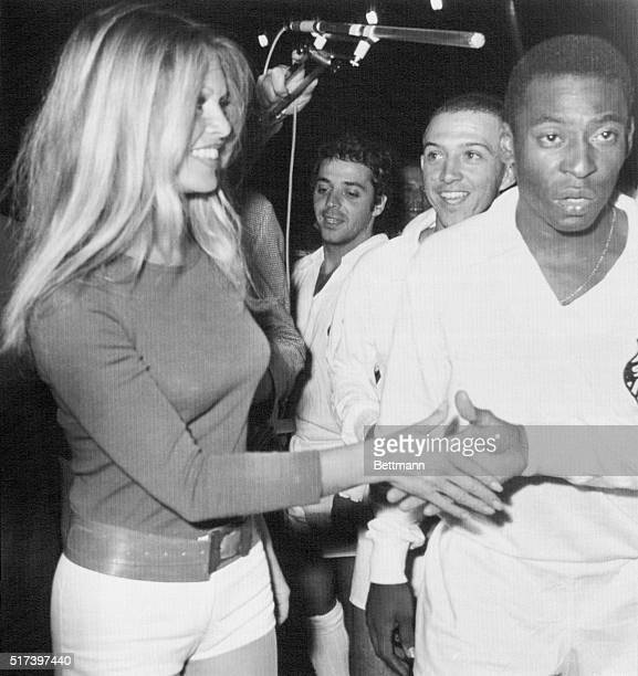 Soccer king Pele , of Brazil, and other team members meet French film star Brigitte Bardot at Colombes Stadium here March 31st during a charity match...