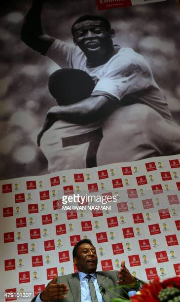 Soccer legend Pele gestures as he sits under a poster of himself jubilating after scoring a goal against Italy in the 1970 World Cup final during a...