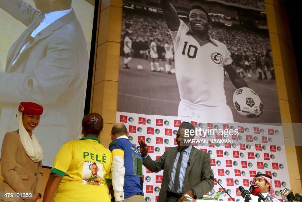 Soccer legend Pele looks at two fans wearing customised Pele Tshirts during a special screening of the iconic Brazilian player's greatest moments at...