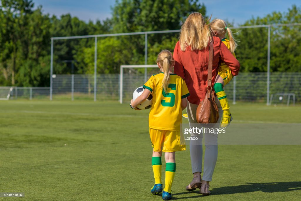 Soccer Mom accompanying her two daughters to football training : Stock Photo