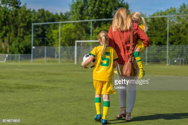 soccer mom accompanying her two daughters to football training - sports equipment stock pictures, royalty-free photos & images