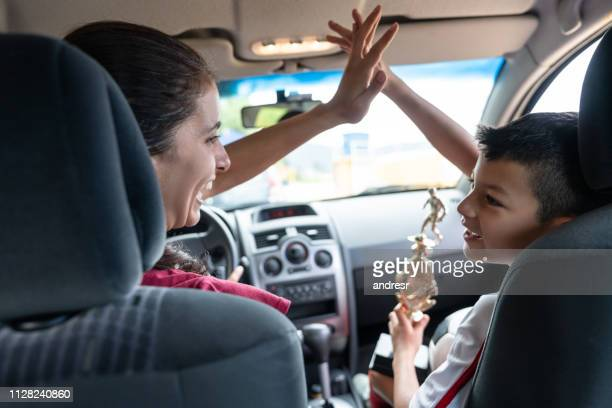 soccer mom getting excited about her son getting a trophy - drive ball sports stock pictures, royalty-free photos & images