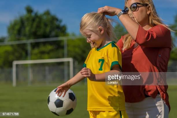 soccer mom preparing her blond daughter for football training - coda di cavallo foto e immagini stock
