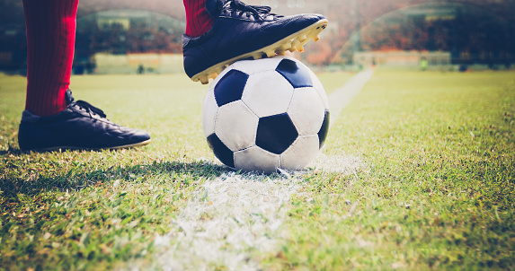 soccer or football player standing with ball on the field for Kick the soccer ball at football stadium 951790474