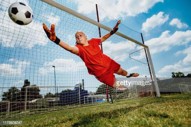voetbal strafschop met tiener vrouwelijke doelman - verdediger voetballer stockfoto's en -beelden