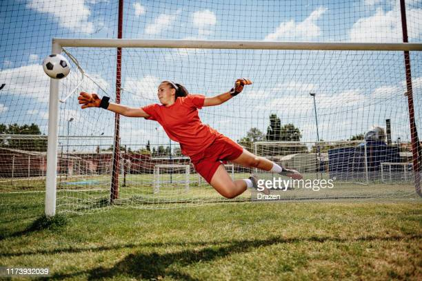 soccer penalty kick with teen female goalkeeper - goalie goalkeeper football soccer keeper stock pictures, royalty-free photos & images