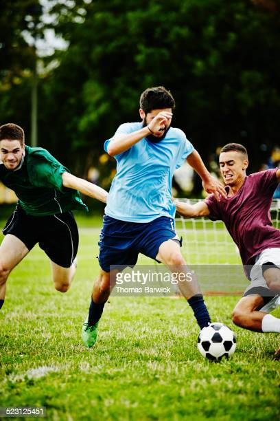 soccer player about to be tackled by opponent - tackling stock pictures, royalty-free photos & images