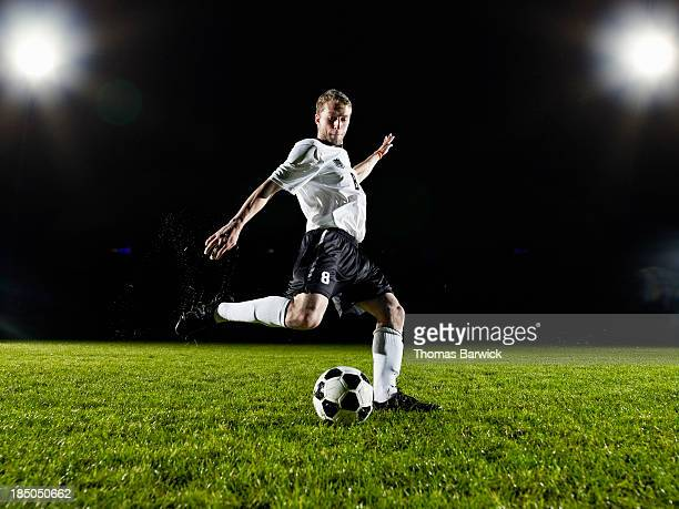 soccer player about to kick ball on field - drive ball sports stock pictures, royalty-free photos & images