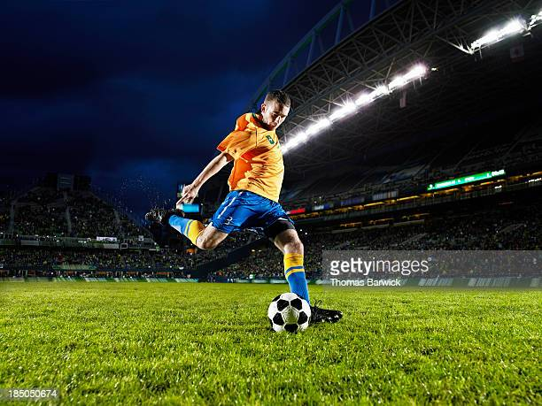 soccer player about to kick ball on field - kicking stock pictures, royalty-free photos & images