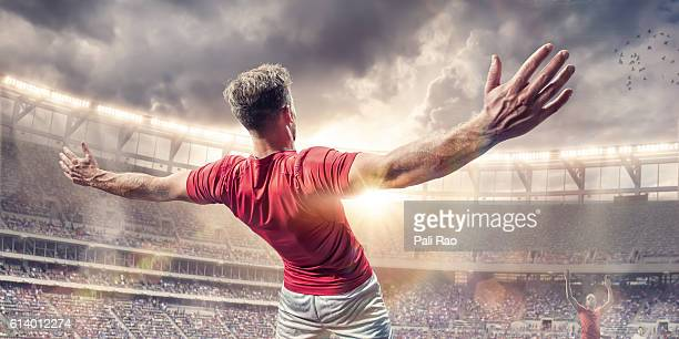 soccer player arms wide celebrating after scoring goal in match - jugador de fútbol fotografías e imágenes de stock