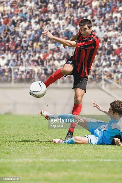 soccer player avoiding a tackle - atacante de futebol imagens e fotografias de stock