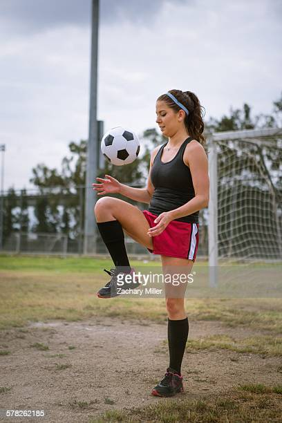 Soccer player bouncing ball on knee in field