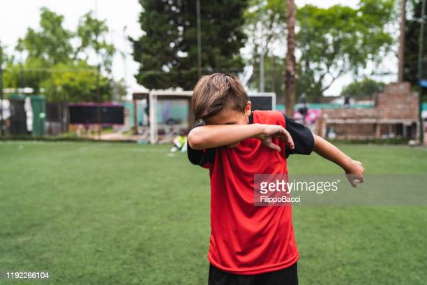 soccer player boy doing the dab dance standing on a soccer field - baby boys stock pictures, royalty-free photos & images