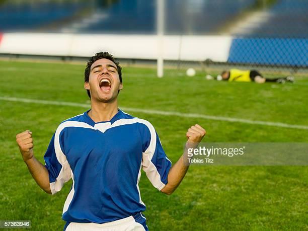 a soccer player celebrating a goal - tor schießen stock-fotos und bilder