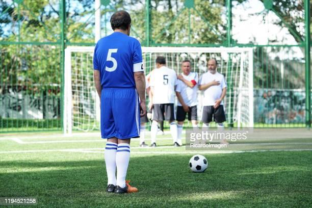 voetbalspeler rekent gratis kick in de wedstrijd met de barrière van het andere team in de voorkant - verdediger voetballer stockfoto's en -beelden