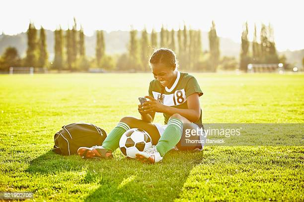 Soccer player checking messages on smartphone