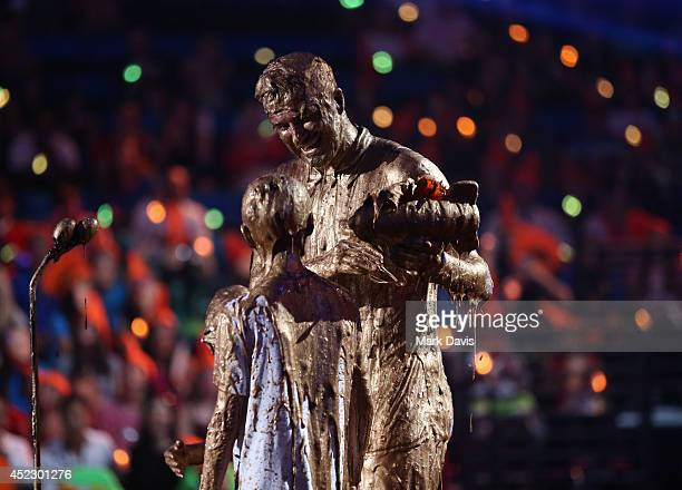 Soccer player David Beckham accepts the Legend Award with Romeo Beckham onstage during Nickelodeon Kids' Choice Sports Awards 2014 at UCLA's Pauley...