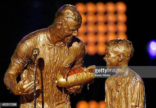 Soccer player David Beckham with Cruz Beckham and Romeo Beckham get slimed onstage during Nickelodeon Kids' Choice Sports Awards 2014 at UCLA's...