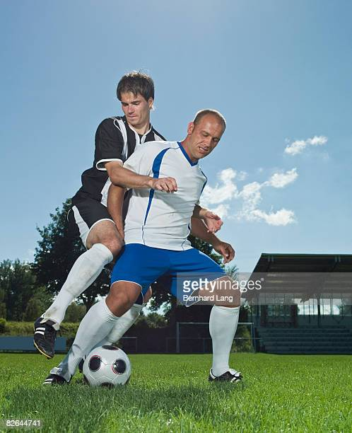 soccer player defending ball against opponent  - tackling stock pictures, royalty-free photos & images
